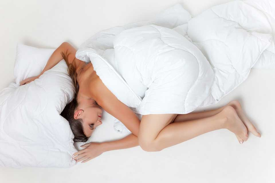 Woman in bed with duvet on top.